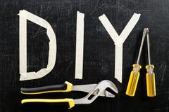 Den bästa sikten av den justerbara skiftnyckeln, skruvmejseln och ordet DIY gjorde intelligens Arkivbilder