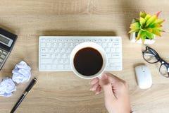 Den bästa sikten av kaffe för koppen för handaffärsmaninnehavet för kopplar av, når den har arbetat på bärbara datorn royaltyfria foton