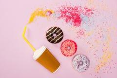 Den bästa sikten av kaffekoppen och variation glaserade donuts på rosa färger Arkivbilder