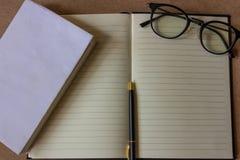 Den bästa sikten av kontorsskrivbordet med tom vit, synförmågaexponeringsglas, mobiltelefonen, pennan och minnestavlan på kork bo Royaltyfri Bild