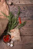 Den bästa sikten av kryddig peppar för den varma chili i en krus, doftande rosmarin och tömmer skal av vaktelägg på en träbakgrun Arkivfoton