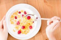 Den bästa sikten av kvinnan som äter mysli med jordgubben och, mjölkar Arkivfoto