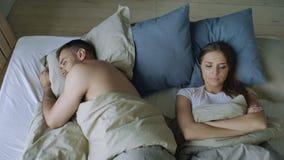 Den bästa sikten av liggande sömnlösa par för rubbningen i säng som kränks på grund av, grälar stock video