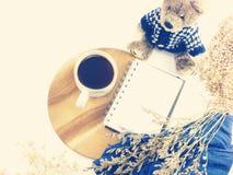 Den bästa sikten av morgonkaffe rånar anteckningsboken och det torkade filtret för färg för blommatappning retro Royaltyfri Foto