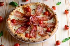 Den bästa sikten av neapolitan pizza med bacon, mozzarella och körsbärsröda tomater, tjänade som på en trätabell Italien mat clos fotografering för bildbyråer
