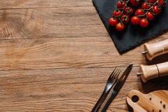 den bästa sikten av nya mogna tomater kritiserar på brädet, gaffeln med kniven, smaktillsatser i behållare och pepparkorn på trät Royaltyfri Bild