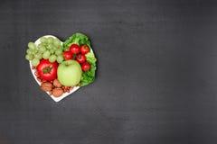 Den bästa sikten av nya organiska grönsaker och frukter på hjärta formade plattan på grå färger Arkivbild