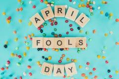 den bästa sikten av ordnade träkuber i bokstäver för dag för april dumbommar på blått ytbehandlar med godisar, 1 april feriebegre Fotografering för Bildbyråer