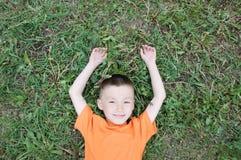 Den bästa sikten av pojken som ligger på gräset på, parkerar att ha gyckel Barnet kopplar av med att le sätta på land tillsammans arkivfoton