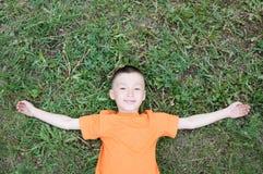 Den bästa sikten av pojken som ligger på gräset på, parkerar att ha gyckel Barnet kopplar av med att le sätta på land tillsammans royaltyfria foton