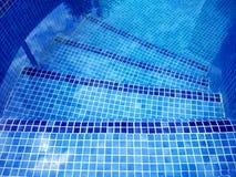 Den bästa sikten av simbassängen buktade trappa med trädreflexion på vattnet royaltyfri foto