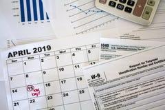 Den bästa sikten av skrivbordet med räknemaskinen, skattformer, grafer och kalenderarket med skattdatumet markerade royaltyfri bild