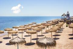 Den bästa sikten av stranden med sugrörparaplyer ror Arkivfoto