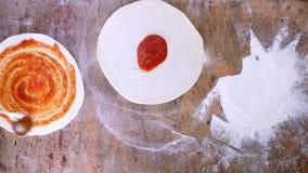 Den bästa sikten av tomatsås suddas över pizzadegen stock video