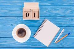 den bästa sikten av träkalendern med datumet av 1st kan, kaffekoppen, den tomma läroboken och pennor, internationellt arbetardagb arkivbild
