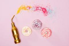 Den bästa sikten av tre glaserade donuts, och den guld- flaskan på rosa färger ytbehandlar Arkivbild