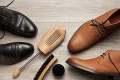 Den bästa sikten av två par av piskar mäns skor och kängor royaltyfria foton