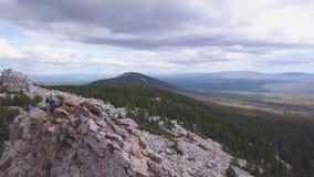 Den bästa sikten av vaggar med turister gem Horisont av bergig terräng med molnig himmel Sikt av turister som klättrar på den ste stock video