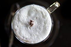 Den bästa sikten av den varma kaffecappuccinokoppen med mjölkar skum Arkivfoto