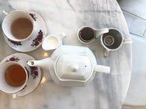 Den bästa sikten av varmt te med mjölkar och skorrar, terasttid marmorerar på tabellen arkivfoto