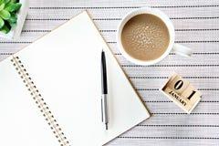 Den bästa sikten eller lägenheten som är lekmanna- av den öppna anteckningsbokpapper, kubkalender och kaffekoppen på tabellbakgru Arkivfoton