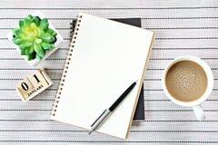 Den bästa sikten eller lägenheten som är lekmanna- av den öppna anteckningsbokpapper, kubkalender och kaffekoppen på tabellbakgru Arkivbilder
