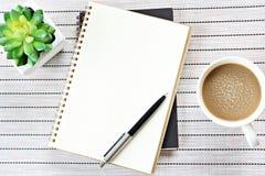 Den bästa sikten eller den lekmanna- bilden för lägenhet av den öppna anteckningsboken med tomma sidor och kaffekoppen på tabellb Royaltyfria Foton