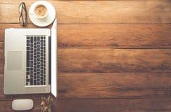 Den bästa sikten har en bärbar dator, kaffe, exponeringsglas på skrivbordet och där Royaltyfri Foto