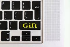 Den bästa sikten isolerade bärbar datortangentbordet med gul text för `-gåva` på knappen, begreppsdesign V royaltyfri foto