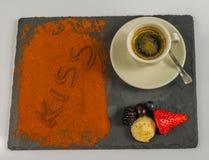 Den bästa sikten på kaffe i en kopp och frukter och ordet kysser Arkivfoto