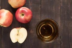 Den bästa sunda äppelmustdrinken och röda äpplen bär frukt på trälodisar Arkivbilder
