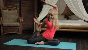 Den böjliga äldre kvinnan utför komplexa övningar på mattt i rum stock video