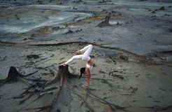 Den böjliga gymnastflickan i ett härligt poserar på en bakgrund av det apokalyptiska landskapet i öknen Royaltyfria Bilder