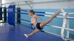 Den böjliga idrottsman nenkvinnan gör sträckning under gymnastisk utbildning för konkurrens i cirkel lager videofilmer