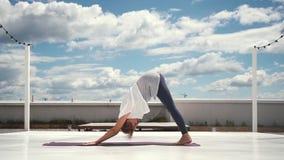 Den böjliga kvinnan gör yoga i ultrarapid i bakgrund av moln och blå himmel stock video