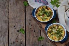 Den bakade eldfasta formen från ägg, bacon, torkade tomater, broccoli och ost i blå ramekin på brun träbakgrund Champinjongratäng Royaltyfri Fotografi