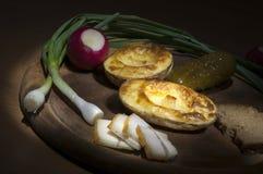 Den bakade potatisen som saltas späcker och löken, den ljusa borsten Arkivfoto