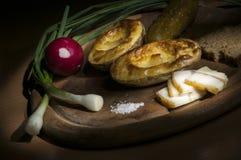 Den bakade potatisen som saltas späcker och löken, den ljusa borsten Arkivfoton