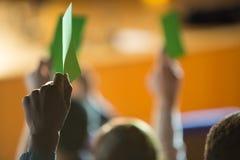 Den bakre sikten av affärsledare visar deras godkännande, genom att lyfta händer arkivfoton