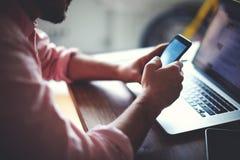 Den bakre sikten av affärsmannen räcker den upptagna användande mobiltelefonen på kontorsskrivbordet Arkivfoton