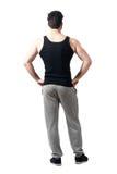 Den bakre sikten av den bärande ärmlös tröja och joggeren för muskulös man flåsar med armar på höfter royaltyfri foto