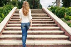 Den bakre sikten av den unga kvinnan som upp går trappa parkerar in Royaltyfri Fotografi