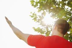 Den bakre sikten av den unga muskulösa mannen som sträcker vid ett träd, en hand och en arm, lyftte in mot himlen och solen i Peki Arkivfoto