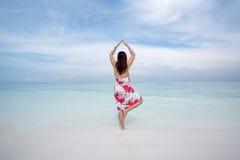 Den bakre sikten av den ursnygga kvinnan i yoga poserar på stranden på ett soligt Arkivbilder
