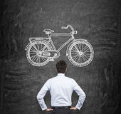 Den bakre sikten av en affärsman i formell kläder, som ser den enorma svarta svart tavlan med ett utdraget, skissar av en cykel E Arkivfoton