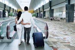 Den bakre sikten av folk går i flygplatskorridor Arkivbild