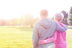 Den bakre sikten av höga par i stående armar för sportswear omkring parkerar in royaltyfri foto