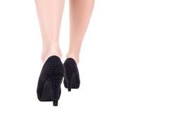 Den bakre sikten av kvinnlign lägger benen på ryggen i svarta skor på häl som går isolaten Arkivbild