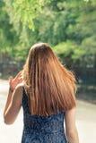 Den bakre sikten av långa haired kvinnor för en rödhårig man som går i stad, parkerar Royaltyfri Foto
