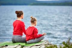 Den bakre sikten av modern och dottern öva yoga på vagga nära floden royaltyfri foto